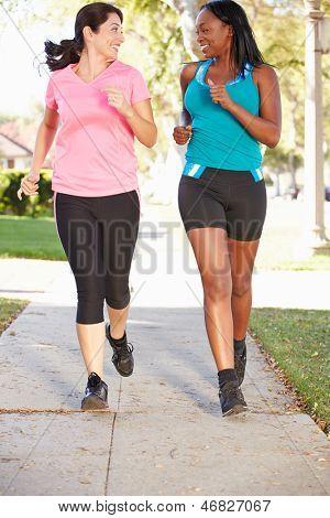 Two Female Runners Exercising On Suburban Street