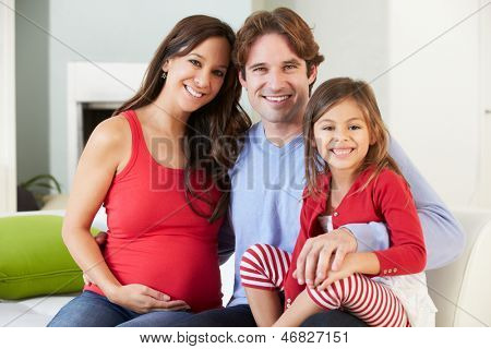 Family With Pregnant Mother Relaxing On Sofa Together