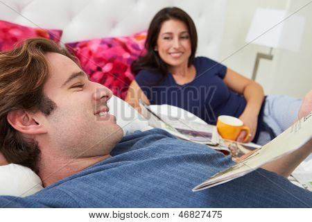 Couple Relaxing In Bed With Coffee And Newspaper