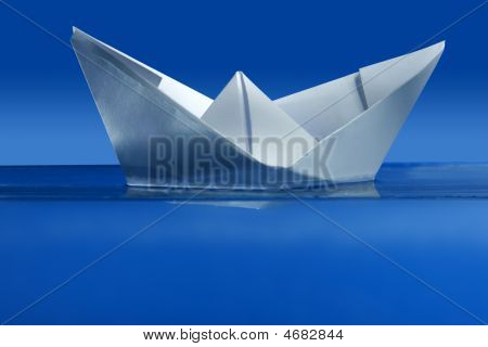 Paper Boat Floating Over Blue Real Water