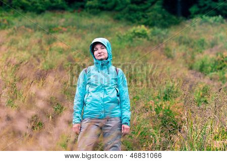 Woman Standing On Grassy Slope