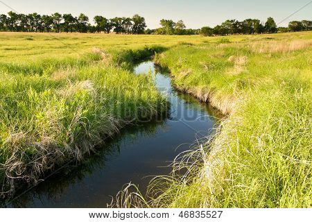 creek winding through Kansas pasture