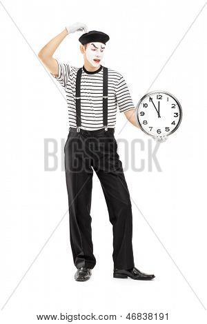 Full length portrait of a mimic holding a clock and thinking, isolated on white background