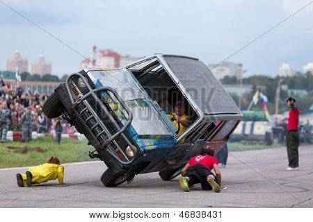 MOSCOW - AUG 25: Stuntman lie under to passing a car on two wheels on Festival of art and film stunt Prometheus in Tushino on August 25, 2012 in Moscow, Russia. The festival was organized in 1998.