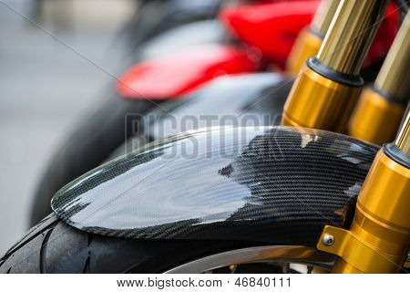 Motorbike detail, carbon fiber mud guard and golden dampers