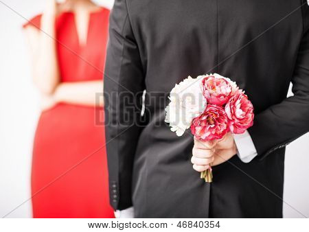 man hiding bouquet of flowers behind his back.