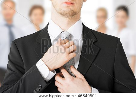 close up of man adjusting his tie