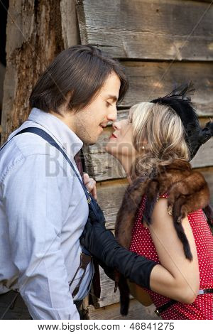 retro couple with woman grabbing his suspenders for kiss