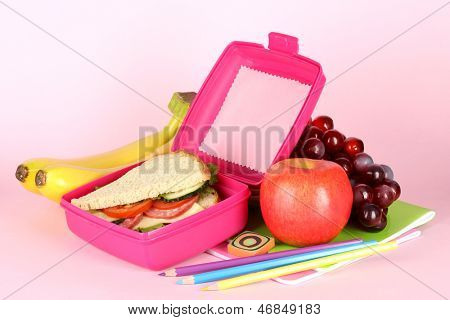 Lunch box with sandwich,fruit and stationery on pink background