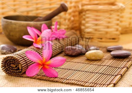 Health spa setting, low light with ambient. Frangipani, hot and cold stone on bamboo mat.