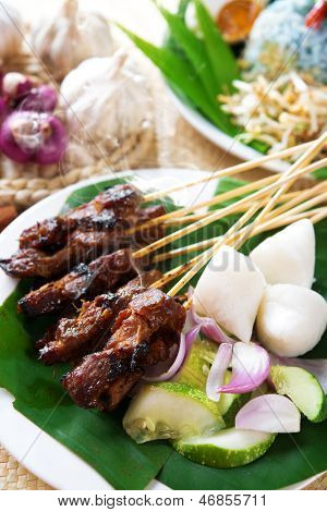 Satay or sate, skewered and grilled meat, served with peanut sauce, cucumber and ketupat. Traditional Malaysian food. Hot and spicy Malay dish, Asian cuisine.