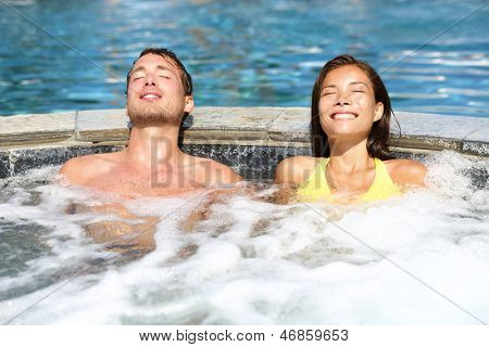 Spa couple relaxing enjoying jacuzzi hot tub bubble bath outdoors on romantic summer vacation travel holidays or honeymoon. Young interracial couple in love, Asian woman, Caucasian man.