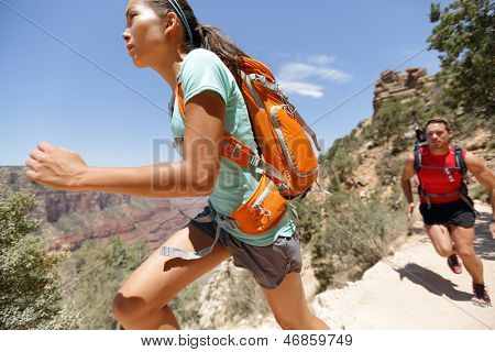 Trail runner woman in cross country running race in Grand Canyon. Couple training working out together sprinting fast at speed in beautiful landscape nature in Grand Canyon, Arizona, USA.