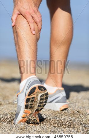 Muscle injury - Man running clutching his calf muscle after spraining it while out jogging on the beach. Male athlete sport injury.