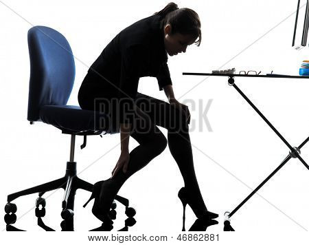 one business woman massaging her leg  silhouette studio isolated on white background
