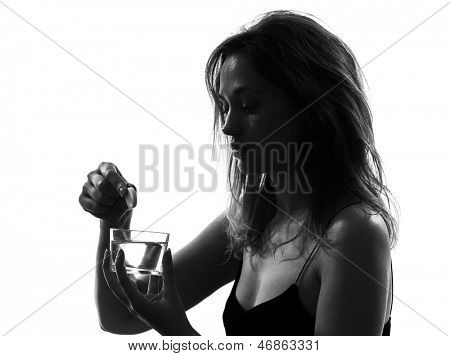 one woman taking effervescent medicine portrait silhouette studio on white background