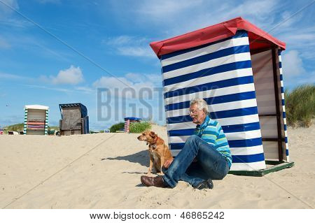Man sitting with dog at the beach of German wadden island with typical striped chair