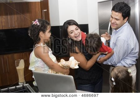 Portrait Of Beautiful Family Playing In Kitchen