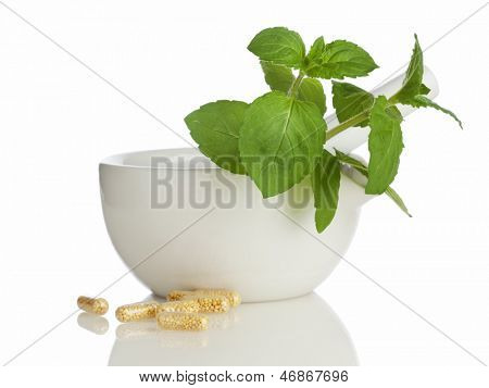 Mortar and pestle with medicine capsules and mint leaves isolated