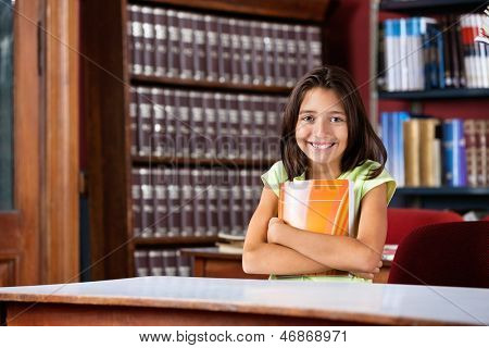 Portrait of happy little schoolgirl holding book while sitting at table in library