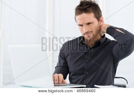 Zakenman moe die op Laptop werkt