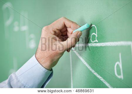 Closeup of mature teacher's hand writing alphabet on greenboard in classroom