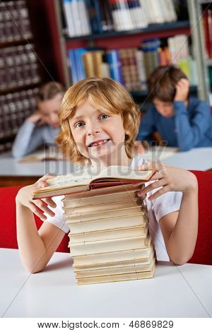 Portrait of cute little schoolboy smiling sitting with stack of books at table in library