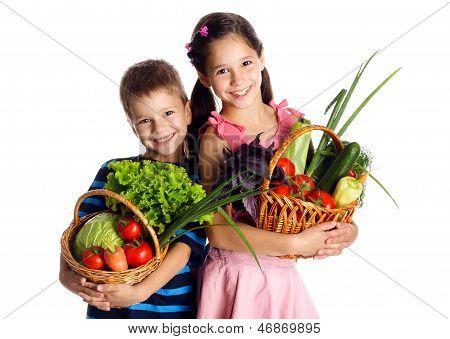 Smiling kids with vegetables in basket