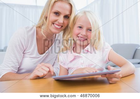 Mother and daughter using tablet pc together in the living room