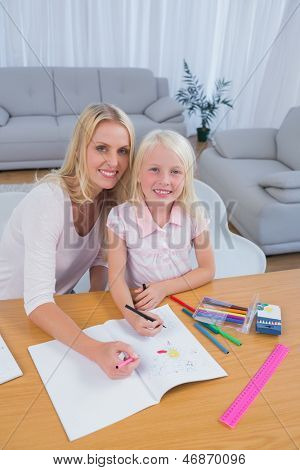 Smiling mother drawing with her little girl in the living room