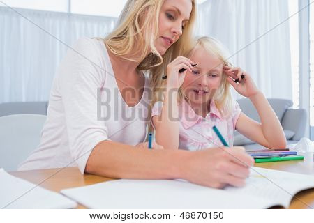 Cute little girl with her mother drawing in the living room