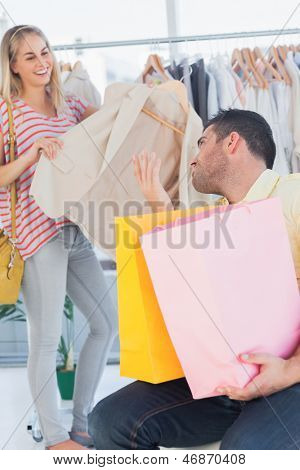 Upset man looking at his shopaholic girlfriend in a clothing star