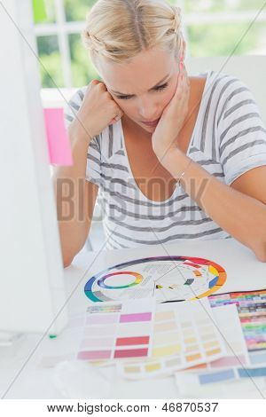 Thoughtful interior designer looking at a colour wheel on her desk with colour charts
