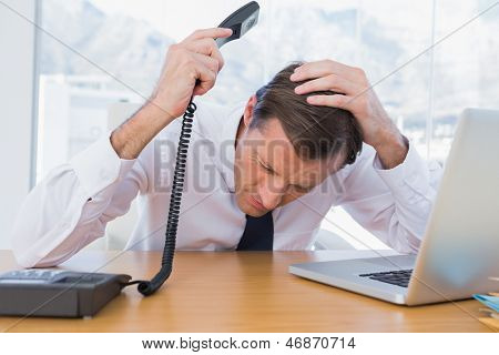 Annoyed businessman holding the telephone in his office