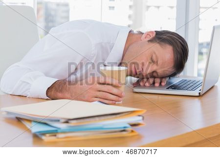 Businessman sleeping on a laptop while he is holding a cup of coffee