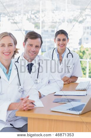 Cheerful doctors posing at their desk with x ray and a laptop computer