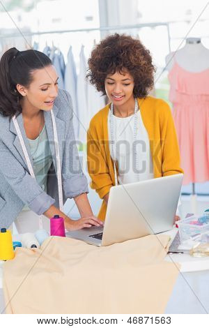 Cheerful fashion designers working on a laptop in a creative office