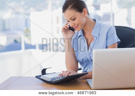 Happy businesswoman calling with her mobile phone and looking at diary at her desk