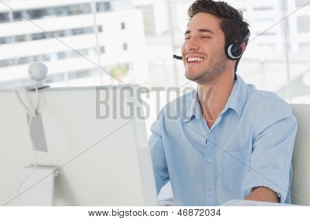 Happy designer laughing during an online communication in his office
