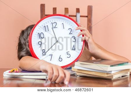 Tired child sleeping on a desk full of books and holding a clock in place of her face to symbolize tiredness after studying too much