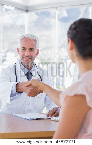 Cheerful doctor shaking hands to patient in the office