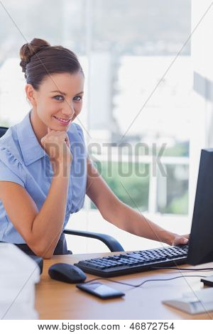Smiling businesswoman working on her computer in her office