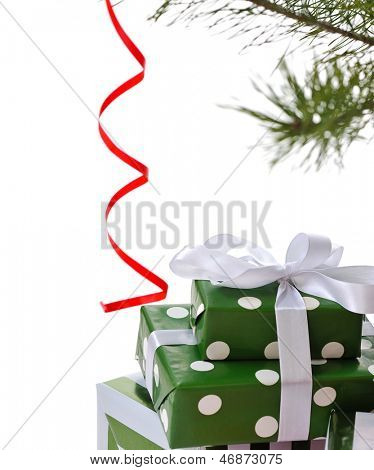 heap green gift boxes  ornated with satin bow  under  Christmas tree