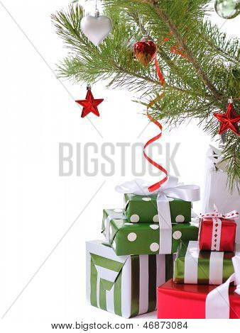 heap of  gift boxes  ornated with satin bow  under decorated Christmas tree