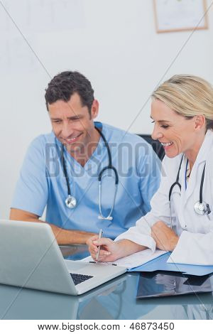 Two doctors working together on a laptop in a medical office