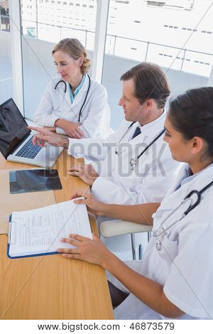 Overview of doctors working together on a laptop on a desk with an x ray