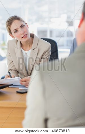 Smiling businesswoman looking at interviewee in the office
