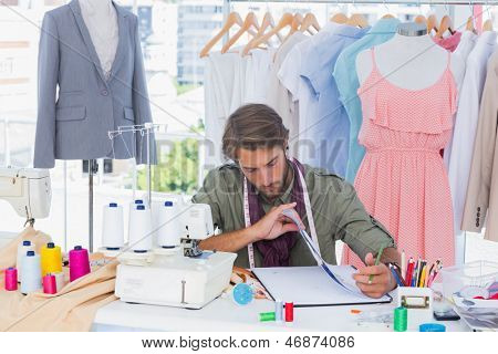 Fashion designer sitting behind a desk with spools of thread and sewing machine