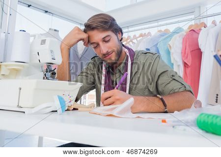 Smiling fashion designer working at his desk in a creative office