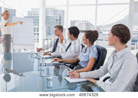 Businesswoman pointing at a colleague who is asking something during a meeting